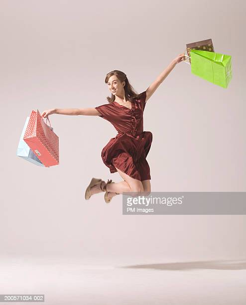 Young woman jumping in air with shopping bags, smiling