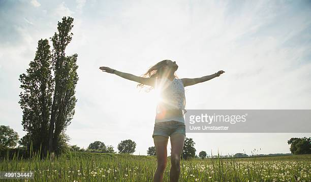 Young woman jumping in field