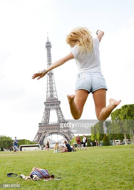 Young woman jumping in front of Eiffel Tower