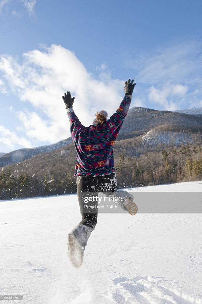 Young woman jumping in the snow