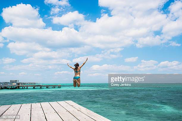Young woman jumping into ocean, San Pedro, Belize