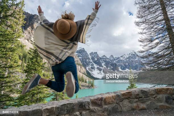 Young woman jumping mid-air by the mountain lake