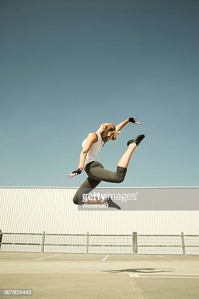 Young woman jumping mid-air on parking level