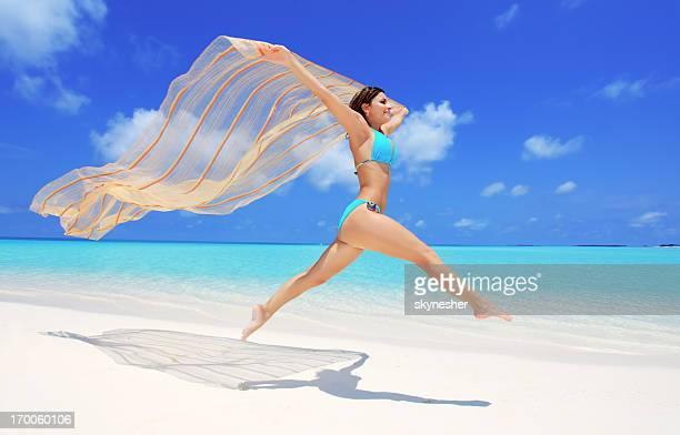 Jovem saltar na praia com um Sarão