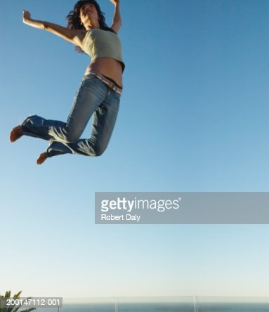 Young woman jumping on trampoline, arms outstretched, low angle view