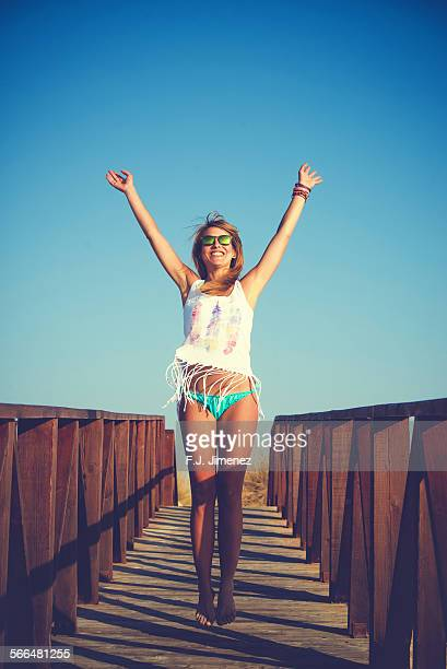 Young woman jumping on wooden path to the beach