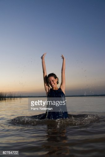 Young woman jumping out of the water at dusk