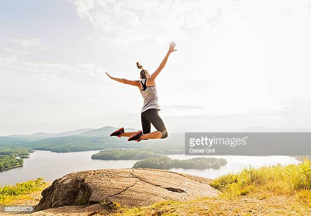 Young woman jumping over mountain top, rear view