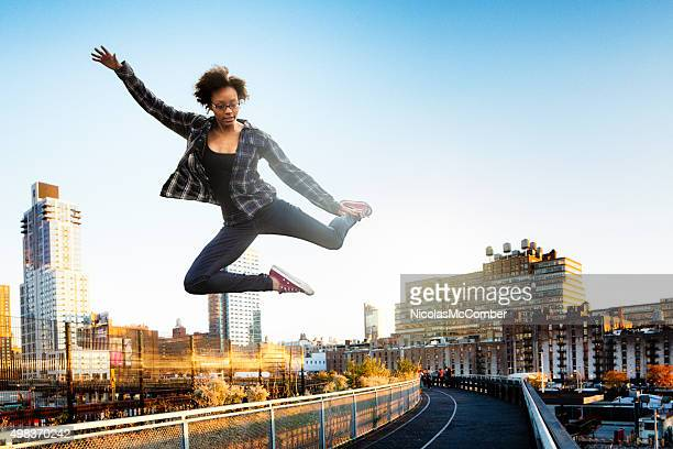 Young woman jumping over New York City High Line park