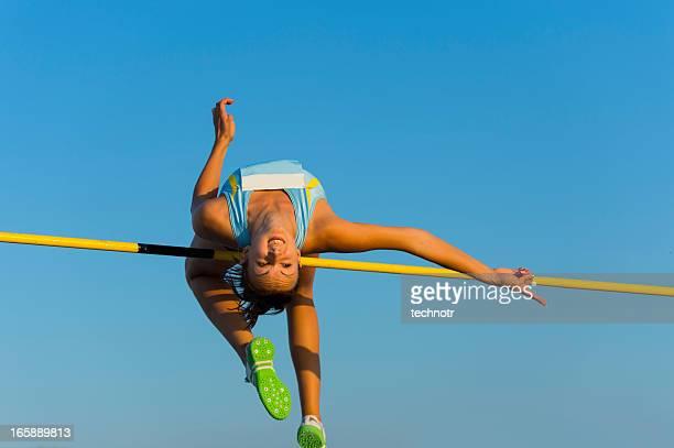 Giovane donna saltando sopra il lath durante la gara