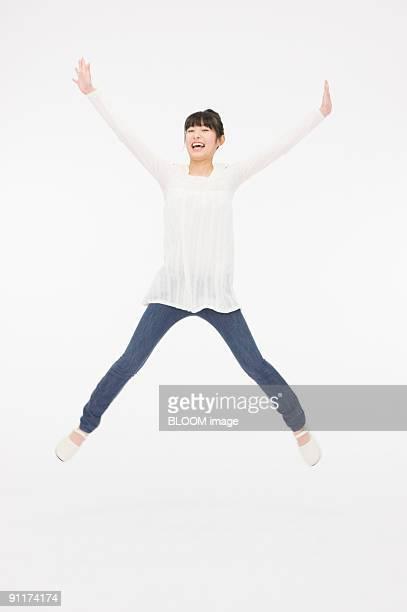 Young woman jumping, raising hands