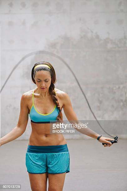 Young woman jumping rope in urban setting