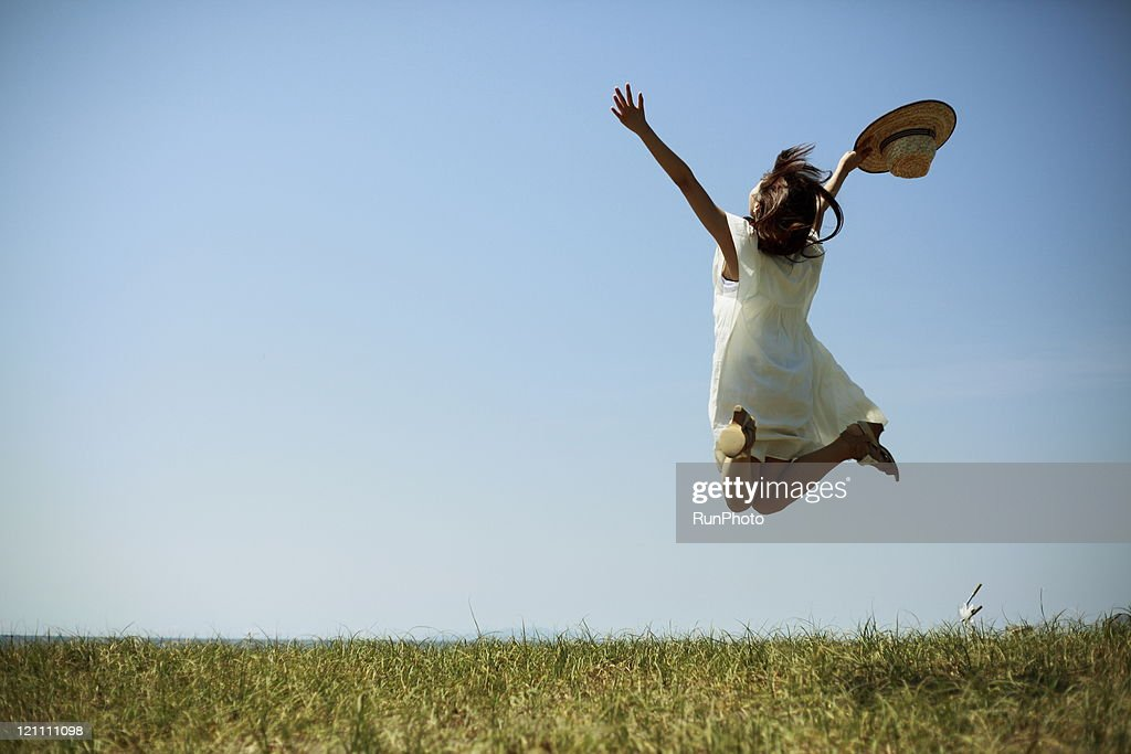 young woman jumping under the sun : Stock Photo