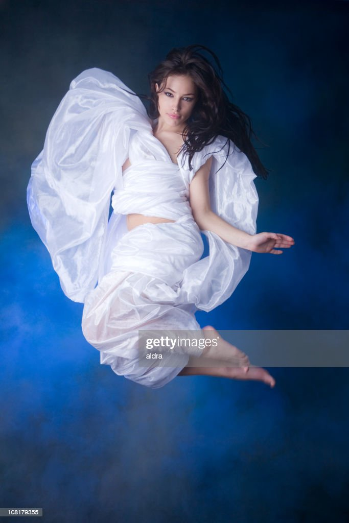 Young Woman Jumping Wearing White Sheet Toga