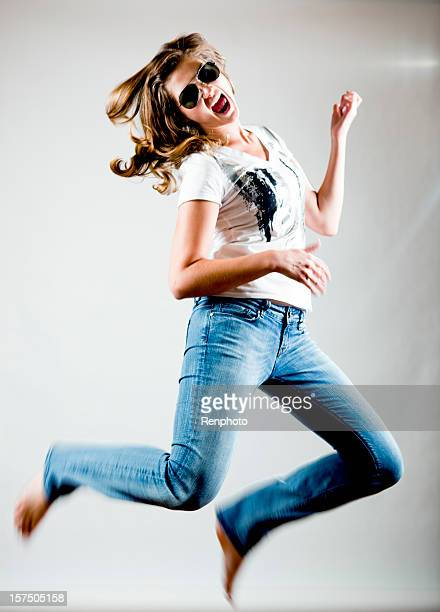 Young woman jumping while doing air guitar