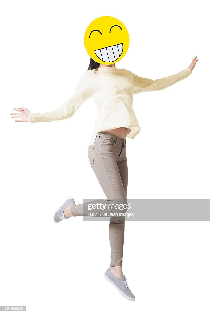 Young woman jumping with a happy emoticon face in front of her face