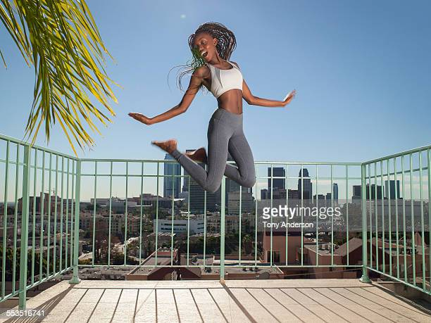 Young woman jumping with city in background