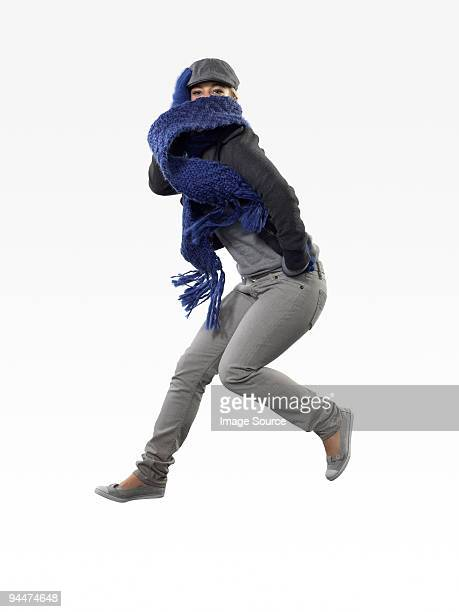 Young woman jumping with scarf over face