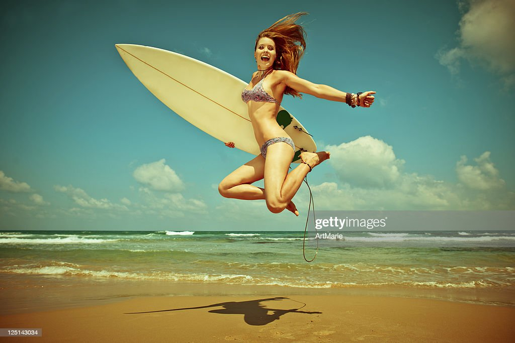 Young woman jumping with surf-board on the beach : Stock Photo