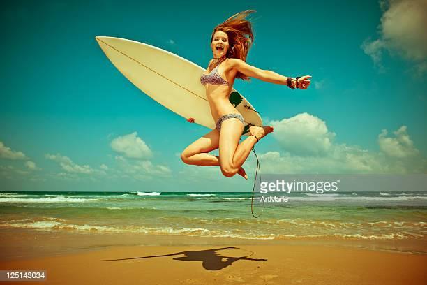 Giovane donna saltando con surf board in spiaggia