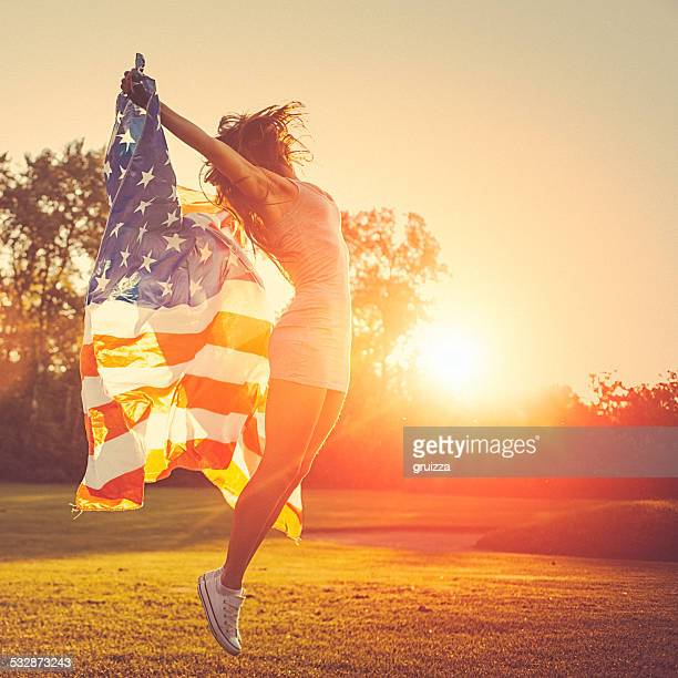 Young woman jumps in a meadow holding american flag