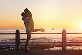 Young woman jumps on boyfriend and gives him a kiss at sunset, romantic passionate moment on date, golden sun flare