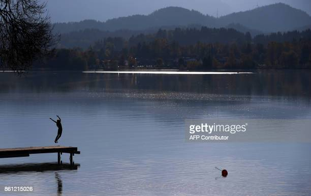 A young woman jumps into the water of the Forggensee lake near Schwangau southern Germany on October 13 2017 / AFP PHOTO / dpa / KarlJosef...