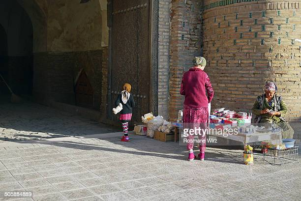 CONTENT] Young woman just bought something old woman counts money Outside Khiva East Gate Polvon Darvoza