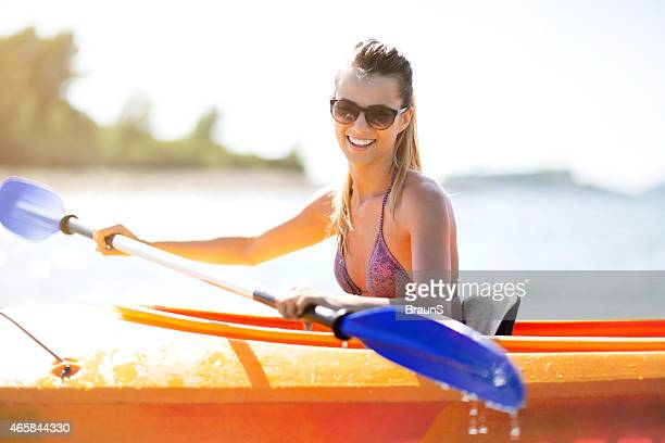 Young woman kayaking during summer day.