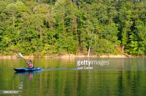 Young woman kayaking on lake in summer