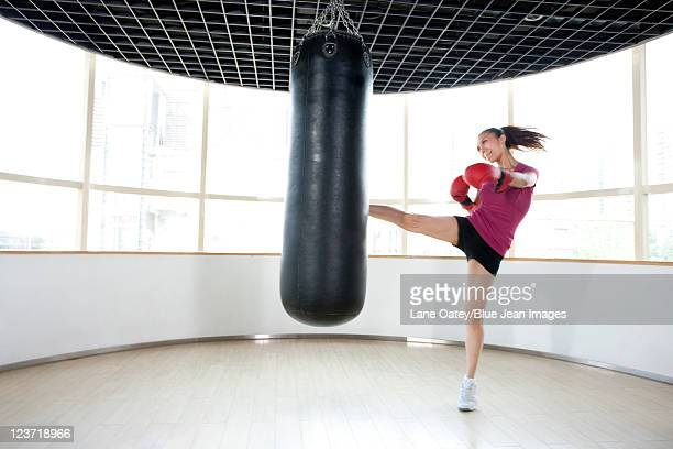 Young Woman Kicking Punching Bag
