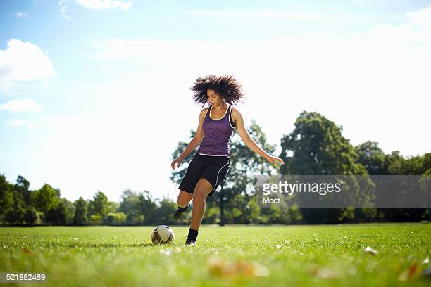Young woman kicking soccer ball in park