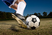 Young woman kicking soccer ball, low section (blurred motion)