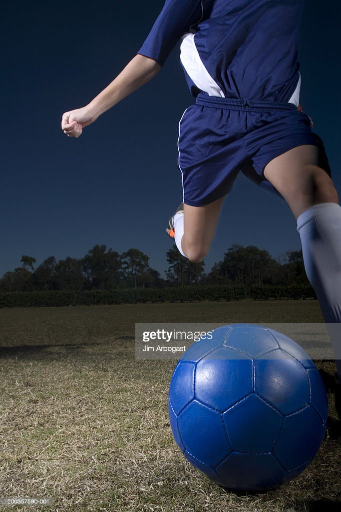 Young woman kicking soccer ball, low section : Stock Photo