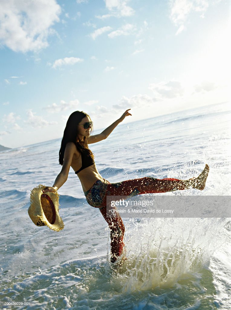 Young woman kicking water in sea, side view : Stock Photo