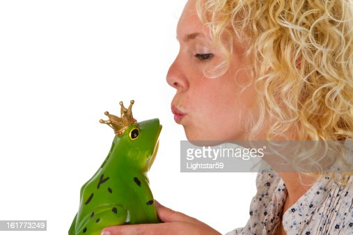 Young woman kissing a frog prince : Stock Photo
