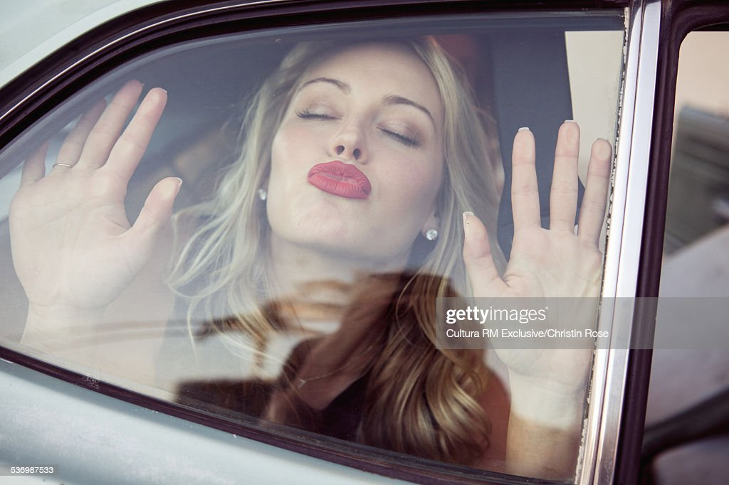 Young woman kissing car window
