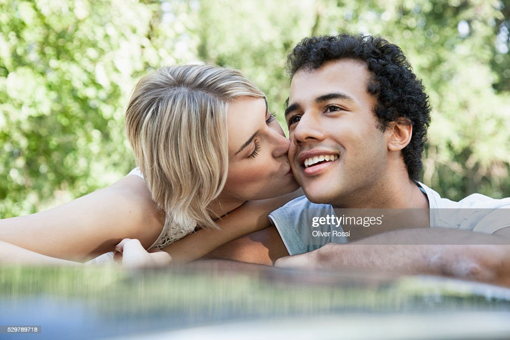 Young woman kissing her boyfriend : Bildbanksbilder