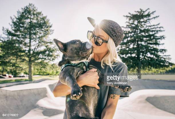 Young woman kissing her dog at skatepark