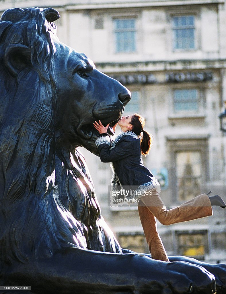 Young woman kissing lion statue, side view : Stock Photo