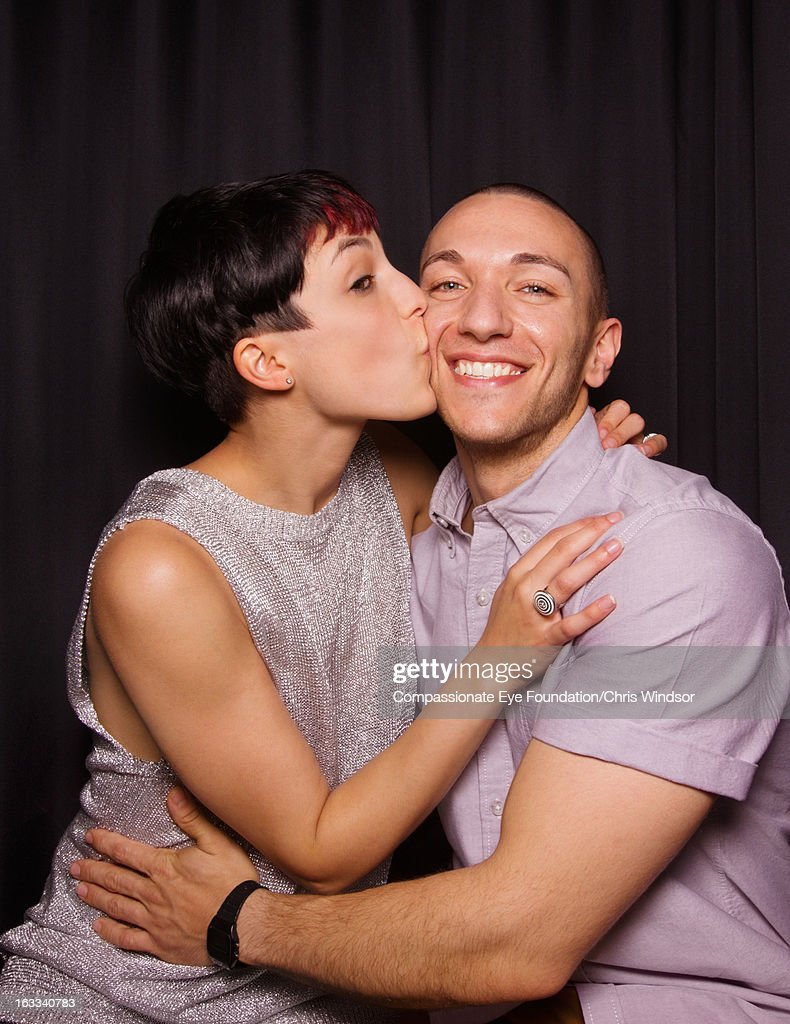 Young woman kissing man on cheek in photo booth : Stock Photo