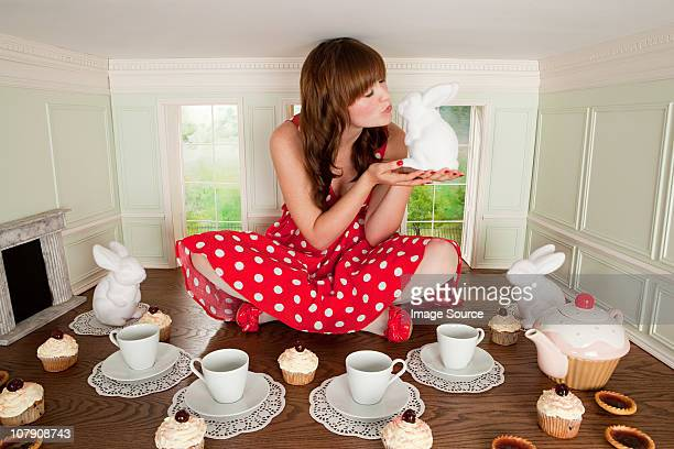 Young woman kissing rabbit at tea party in small room
