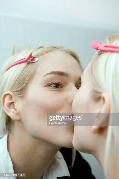Young woman kissing reflection in mirror