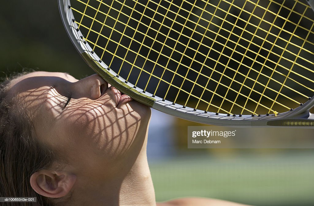 Young woman kissing tennis racket, outdoors, close-up : Stock Photo