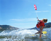 Young woman kiteboarding, skimming hand across water (blurred motion)