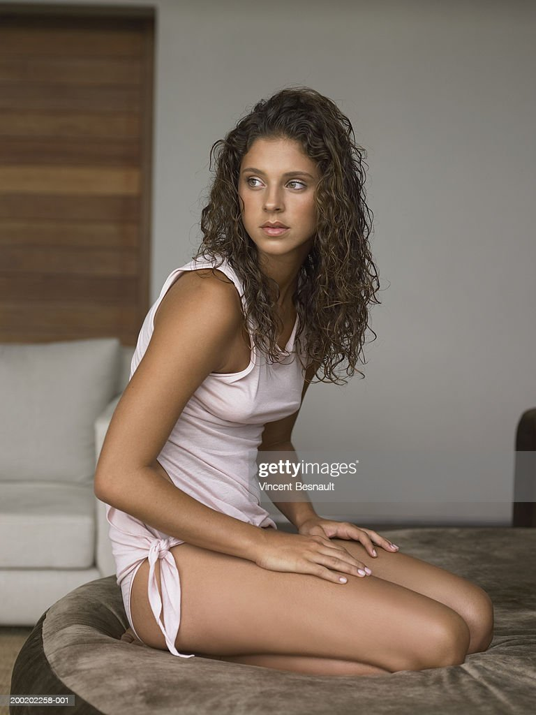 Woman kneeling on large pouffe looking away stock photo getty images