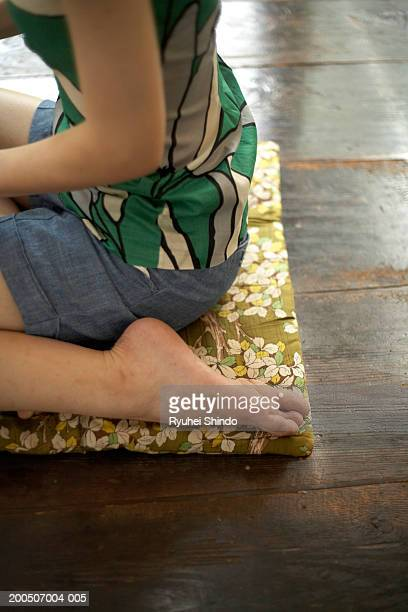 Young woman kneeling on tatami, side view, mid section