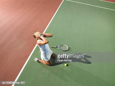 Young woman kneeling on tennis court, hand in hands