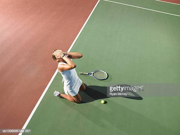 Young woman kneeling on tennis court, hand in hands
