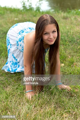 Young woman kneeling on the grass by the river : Stock Photo
